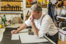 Saddler cutting piece of leather with stencil — Stock Photo