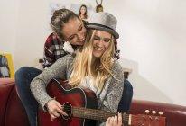 Dos amigas tocando la guitarra juntos en casa - foto de stock