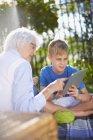 Внук и бабушка используют цифровой планшет в парке — стоковое фото