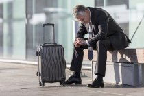 Exhausted businessman with baggage sitting outside airport building — Stock Photo
