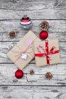 Cadeaux de Noël enveloppés, boules de Noël et cônes de sapin sur bois — Photo de stock