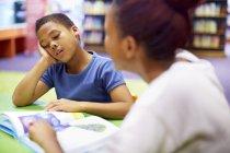 Jeune institutrice et garçon réticent à table — Photo de stock