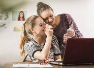 Deux amies riantes utilisant un smartphone et un ordinateur portable à la maison — Photo de stock