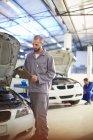 Car mechanic with clipboard in repair garage — Stock Photo