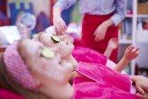 Chicas en una granja de belleza con máscaras faciales de pepino - foto de stock