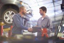 Kfz-Mechaniker und Client Händeschütteln in Autowerkstatt, Auto auf Hintergrund — Stockfoto