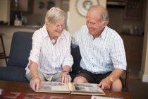 Старший пара з фотоальбом — стокове фото
