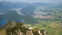 Germany, Bavaria, Swabia, East Allgaeu, Tegelberg, View to top station of Tegelberg Cable Car, and Fuessen, Lech Valley in Austria in the background — Stock Photo