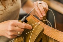 Woman sewing elastic fabric rubber band using lacing pony and awl — Stock Photo
