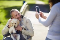 Woman taking picture of man with dog puppy in wheelchair — Stock Photo