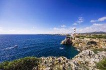 Faro sulla costa rocciosa soleggiata — Foto stock