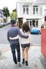 Joven pareja con brazos caminando en la calle - foto de stock