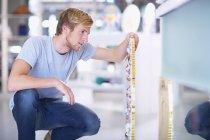 Junger Mann Glasmalerei Produkt prüfen — Stockfoto