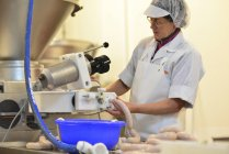 Woman working at sausage production in a butchery — Stock Photo