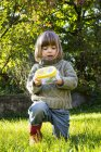 Little girl with insect can on grassy lawn — Stock Photo