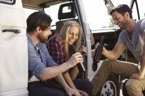 Amigos felizes comemorando com cerveja em minivan — Fotografia de Stock