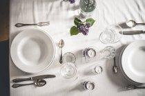 Праздничный накрытый стол украшен сиреневыми цветами — стоковое фото