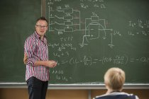 Vocational school student in classroom with teacher at blackboard — Stock Photo