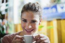 Porträt einer jungen Frau, die in einem Café Kaffee trinkt — Stockfoto