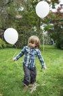 Lindo niño con globos en el jardín - foto de stock