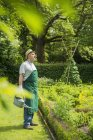 Senior man with watering can at work in green garden — Stock Photo