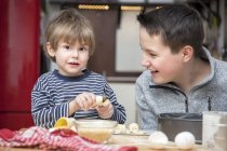 Two brothers baking a cake together at home — Stock Photo