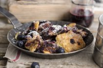 Kaiserschmarren with blueberries on pan over table — Stock Photo