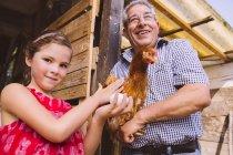 Mädchen Petting Huhn mit großen übergeordneten — Stockfoto