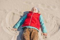 Хлопчик, лежачи на піску на пляжі — стокове фото