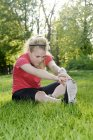 Young woman doing stretching exercise while sitting on meadow — Stock Photo