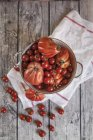 Oxheart and cherry tomatoes in pot — Stock Photo