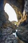 Nouvelle-Zélande, Golden Bay, Wharariki Beach, grotte marine dans les rochers avec un petit ruisseau à marée basse — Photo de stock
