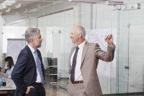 Зрелые бизнесмены обсуждают в современном офисе — стоковое фото