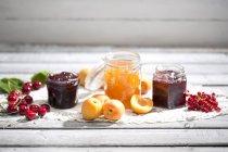 Confitura de cerezas y cerezas, mermelada de albaricoque, albaricoques, mermelada de grosella y grosella en dolly - foto de stock