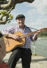 Portrait of old man with guitar at park — Stock Photo