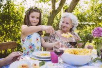 Girl serving pasta to grandmother at garden party — Stock Photo