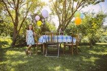 Junge kaukasische Mädchen mit Luftballons im Garten — Stockfoto