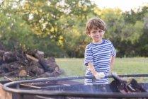 Boy roasting marshmallows over camp fire — Stock Photo