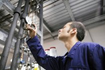 Technician working in a technical room looking at gauge — Stock Photo
