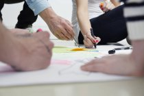 Creative professionals drawing on paper on floor — Stock Photo