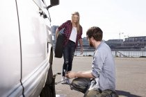 Smiling couple changing car tyre at minivan — Stock Photo