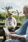 Deux vieillards à l'aide d'ordinateurs tablette dans le parc — Photo de stock