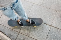 Young female skate boarder standing on her skateboard, partial view — Stock Photo