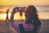 Frau am Strand fotografieren Sonnenuntergang mit ihrem smartphone — Stockfoto