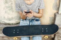 Молода жінка Скейт кордоні з смартфон і скейтборд перед фасадом, частковим видом — стокове фото