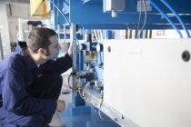 Цілеспрямований технік, які працюють в будівлі заводу — стокове фото