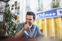 França, Paris, retrato de homem sorridente, sentado num café — Fotografia de Stock