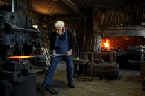 Germany, Bavaria, Josefsthal, senior  blacksmith at work in historic blacksmith's shop — Stock Photo