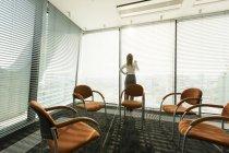 Mulher de negócios no escritório, olhando através das cortinas — Fotografia de Stock