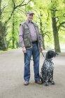 Senior homme avec son chien Braque allemand dans le parc de la ville — Photo de stock
